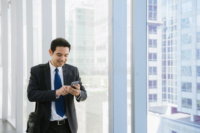 Young businessman in airport. Casual urban professional business man using smartphone smiling happy inside office building. royalty free stock images