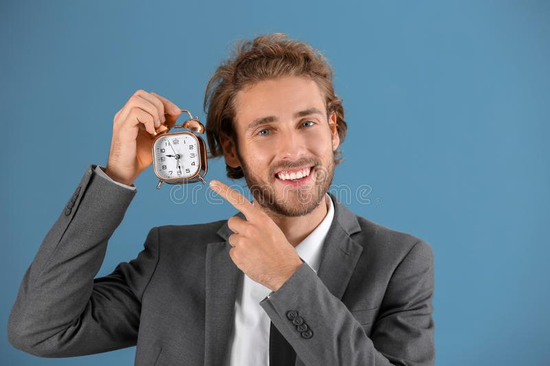 Young businessman with alarm clock on blue background royalty free stock photography