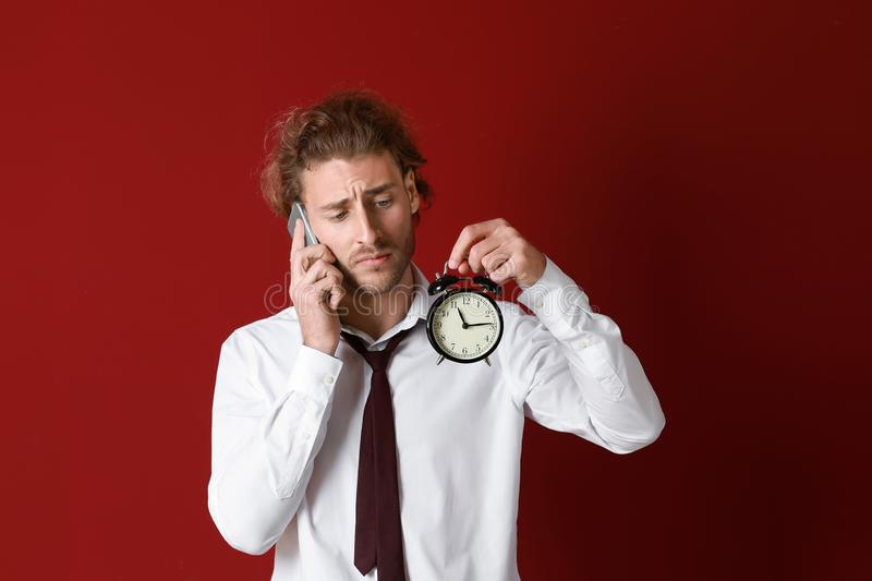 Young businessman with alarm clock talking by mobile phone on color background stock photography
