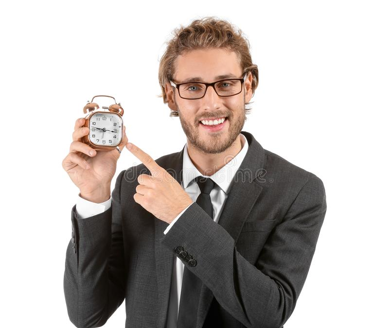 Young businessman with alarm clock on white background stock photography