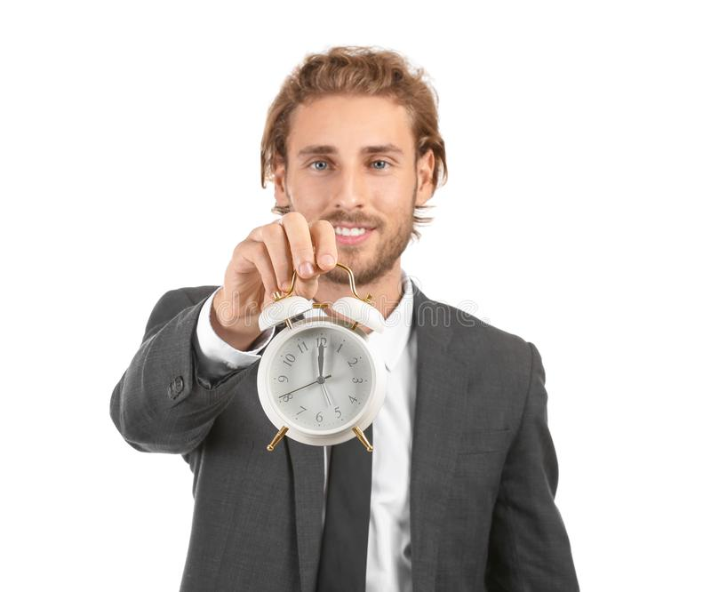 Young businessman with alarm clock on white background royalty free stock images