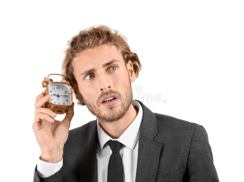 Young businessman with alarm clock on white background royalty free stock photo