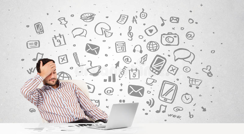 Young businessman with all kind of hand-drawn media icons in background stock photography