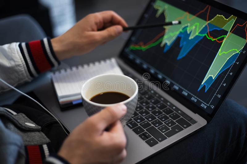 Young businessman analysing finance on laptop with coffe in hand. stock photo
