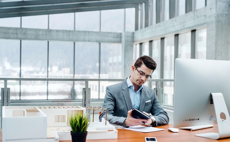 Young businessman or architect with model of a house sitting in office, working. stock photos