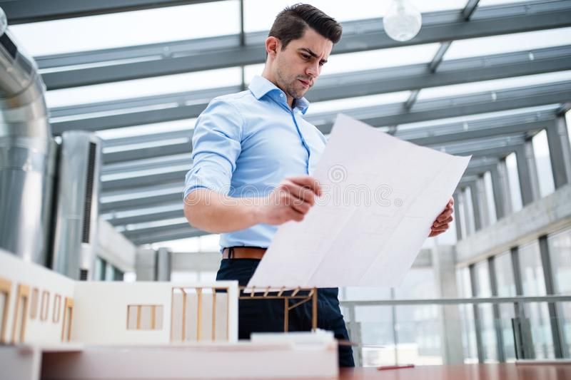 Young businessman or architect with model of a house standing in office, working. royalty free stock photography