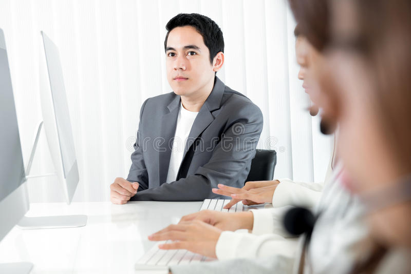 Young businessman as a manager or supervisor sitting beside staff royalty free stock images