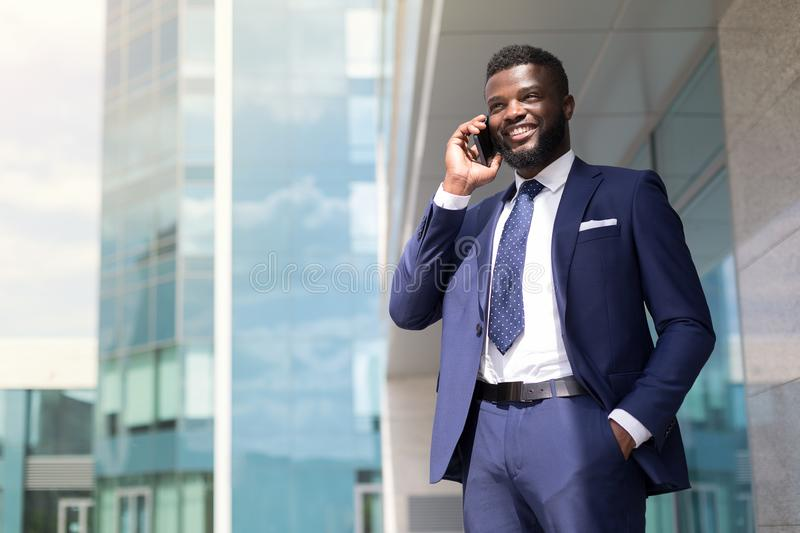 Young businessman with a beard in blue suit speaking on the phone outside with copy space royalty free stock photos