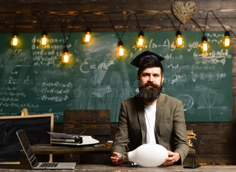 Young businessman with beard wearing suit and thinking. Blackboard background with many lightbulbs lit. Concept of doubt stock photography