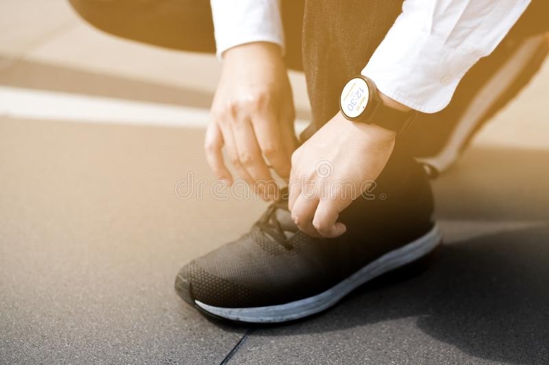 A young businessman bent down to tie his shoes To keep walking stock photo