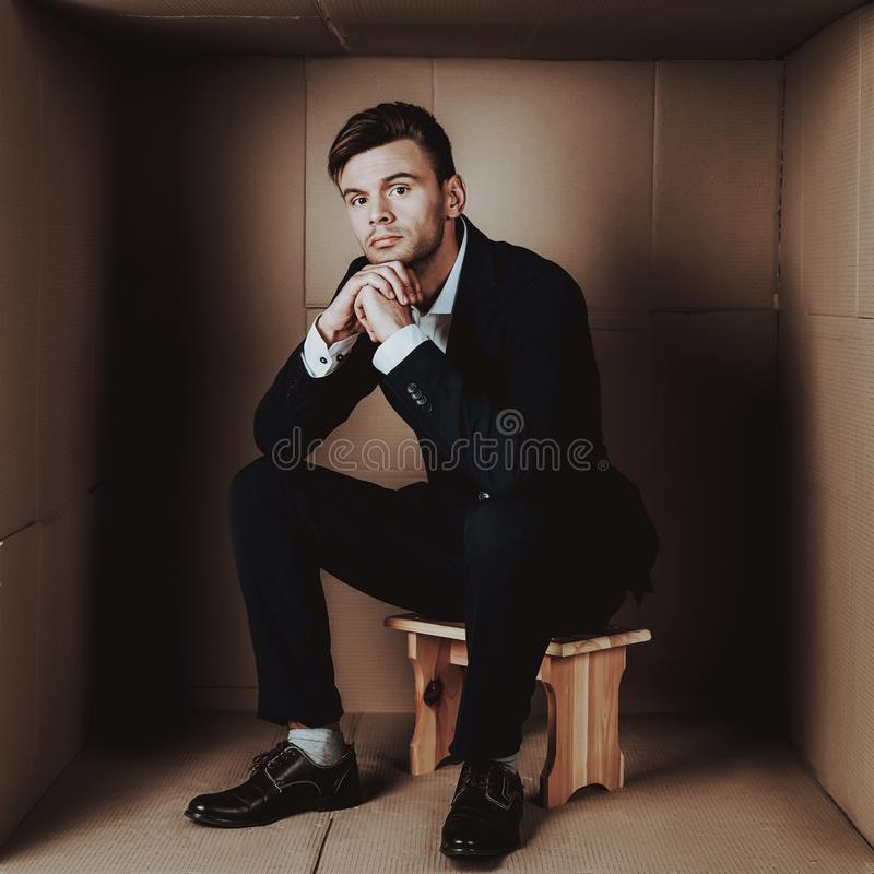 Young Businessman in Black Suit in Cardboard Box. royalty free stock images