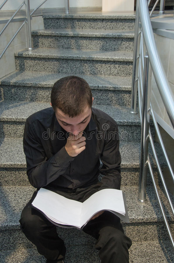 Young businessman in black suit sitting on stairs and reading the documentation papers.  stock image