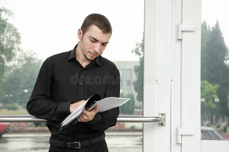 Young businessman in black suit standing and reading the documentation papers. stock photo