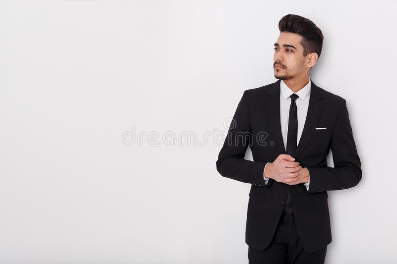 Young businessman in black suit on a white background. Confident man looking away from the camera. royalty free stock photography