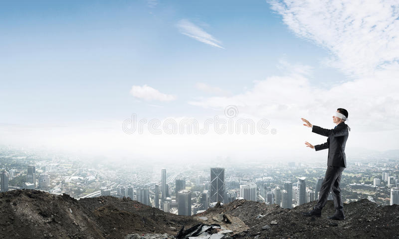 Young businessman in blindfold walking carefully and cityscape at background. Concept of risk and danger in business with man steping blind royalty free stock photos