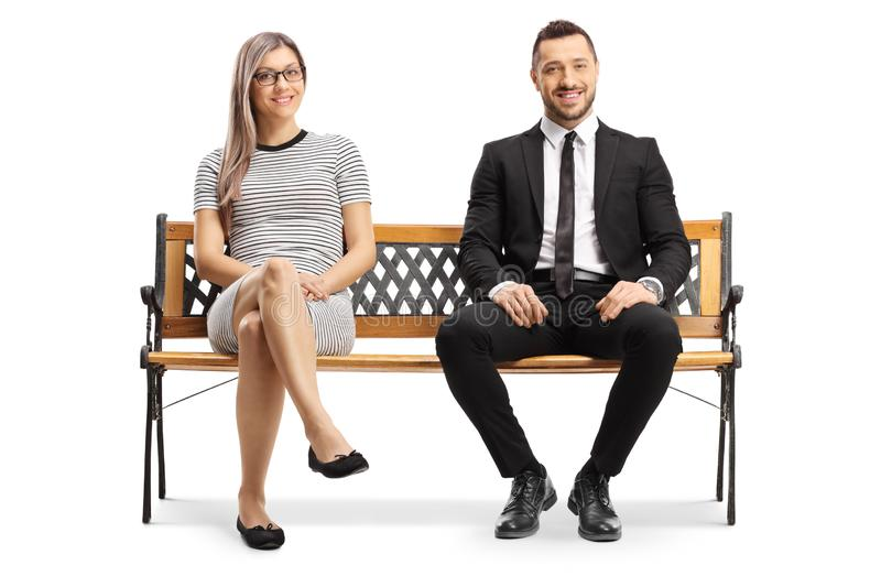 Young businessman and a blond woman sitting on a bench stock photos