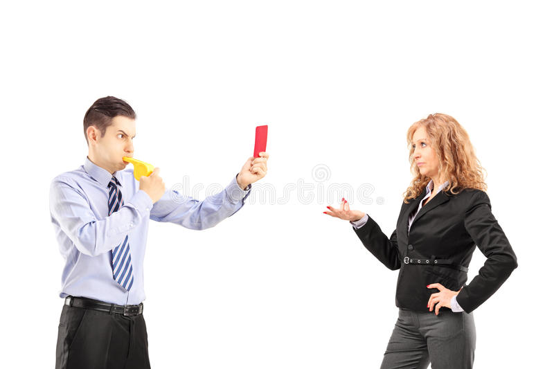 Young businessman blowing a wistle and showing a red card to his stock photography