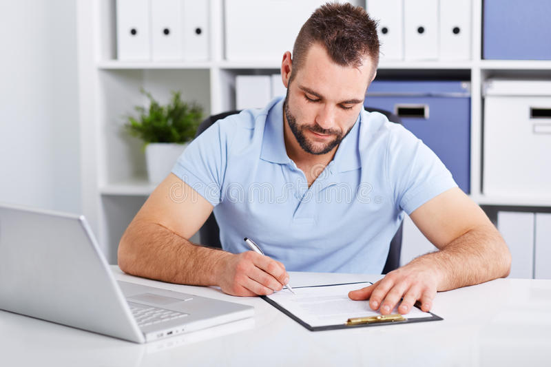 Young businessman in blue polo shirt signs a contract. On white table stock photography