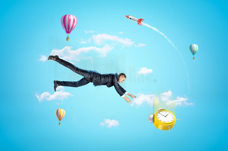 Young businessman in blue sky falling down trying to catch yellow alarm clock, with hot air balloons and rocket in. Background. Be pressed for time. Fail stock photo