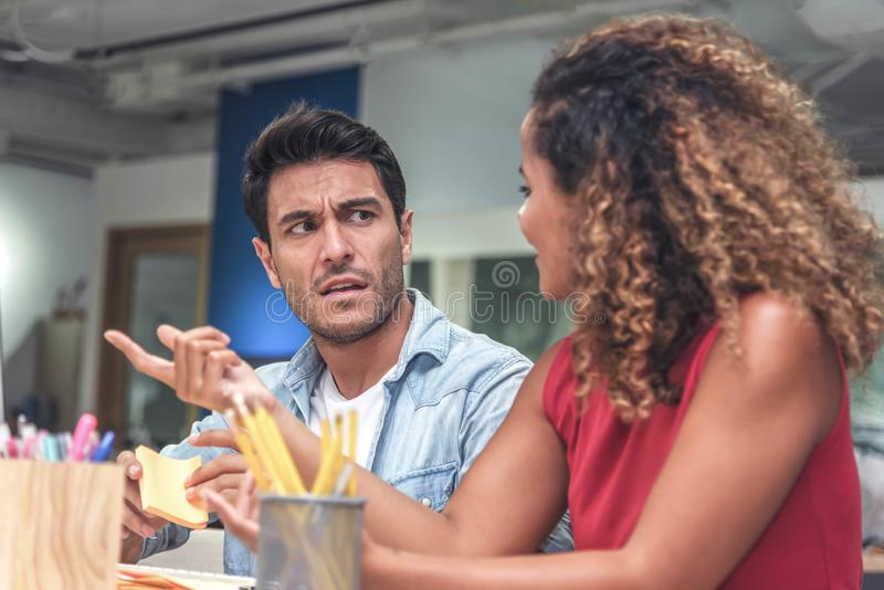 Young businessman and businesswoman in casual clothes having a new project discussion or having an idea at workplace.  stock images