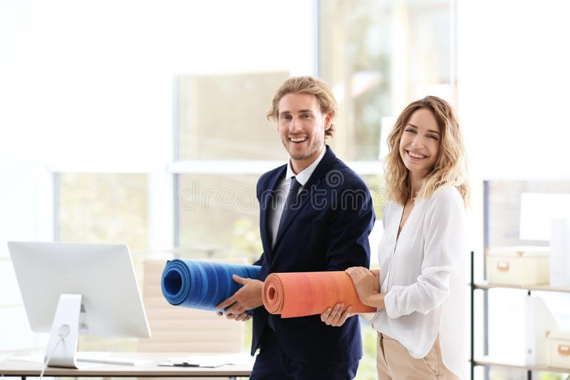 Young businessman and businesswoman holding yoga mats in office stock images