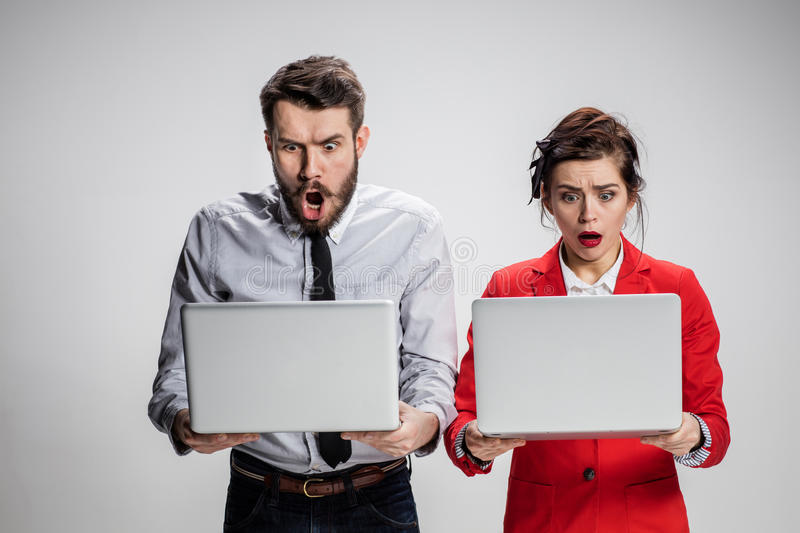 The young businessman and businesswoman with laptops communicating on gray background. The young astonished businessman and businesswoman with laptops royalty free stock photography