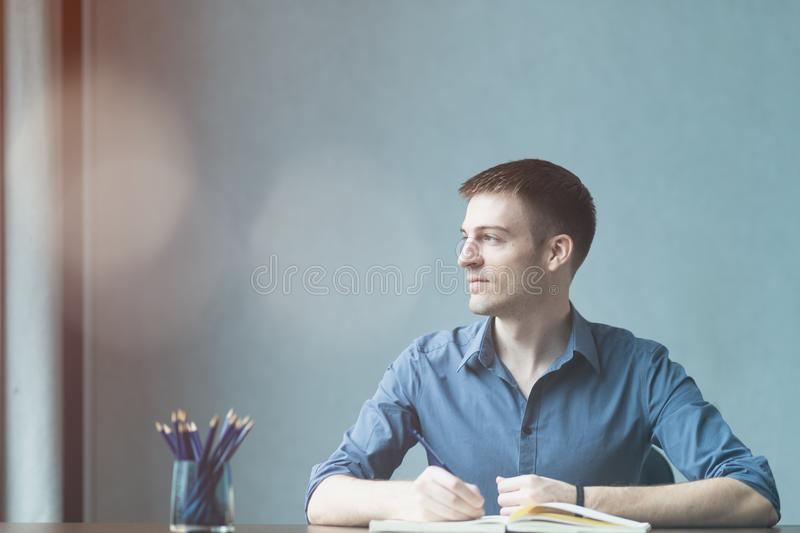 Young businessman caucasians sitting at desk office table and taking notes in notebook. Writing and looking out the window. On the left and happy smile while royalty free stock photography