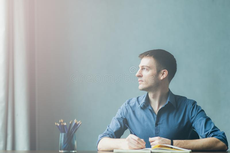 Young businessman caucasians sitting at desk office table and taking notes in notebook. Writing and looking out the window. On the left and happy smile while stock photography