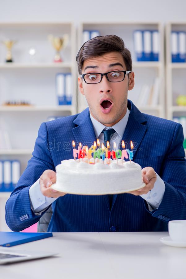 The young businessman celebrating birthday alone in office. Young businessman celebrating birthday alone in office stock photos