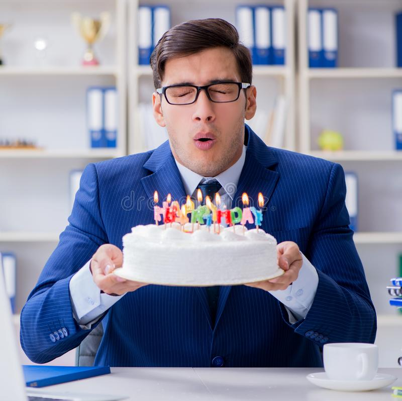 Young businessman celebrating birthday alone in office. The young businessman celebrating birthday alone in office stock photography