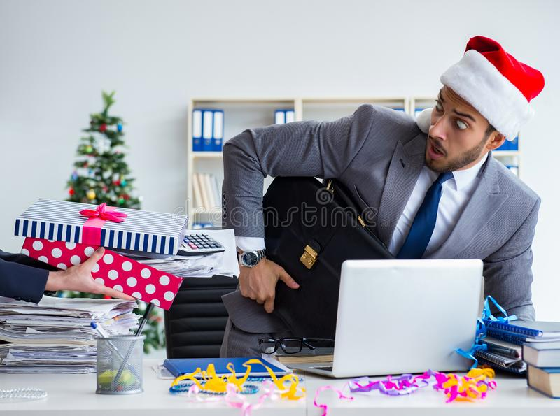 Young businessman celebrating christmas in the office. The young businessman celebrating christmas in the office stock photo