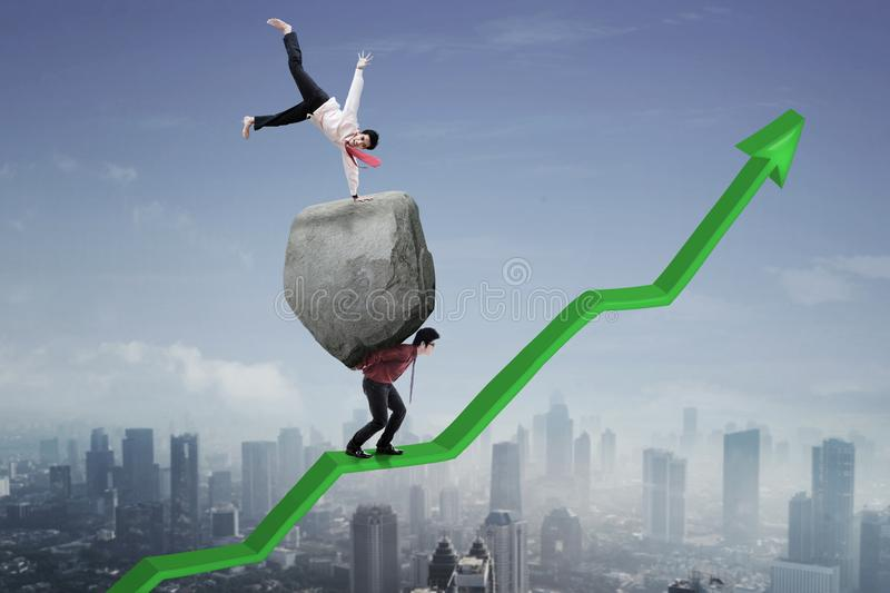 Successful businessman with his partner on upward an arrow. Young businessman celebrating his success above stone while his partner walking on an upward arrow stock photos