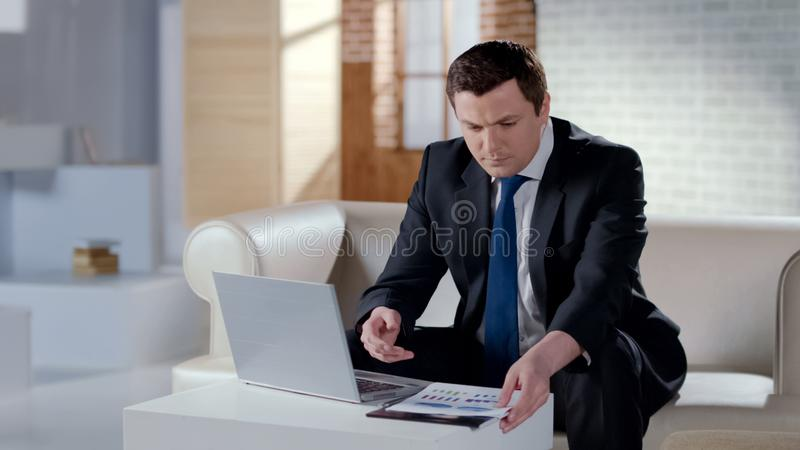 Young businessman checking financial report, working on laptop in modern office royalty free stock photography