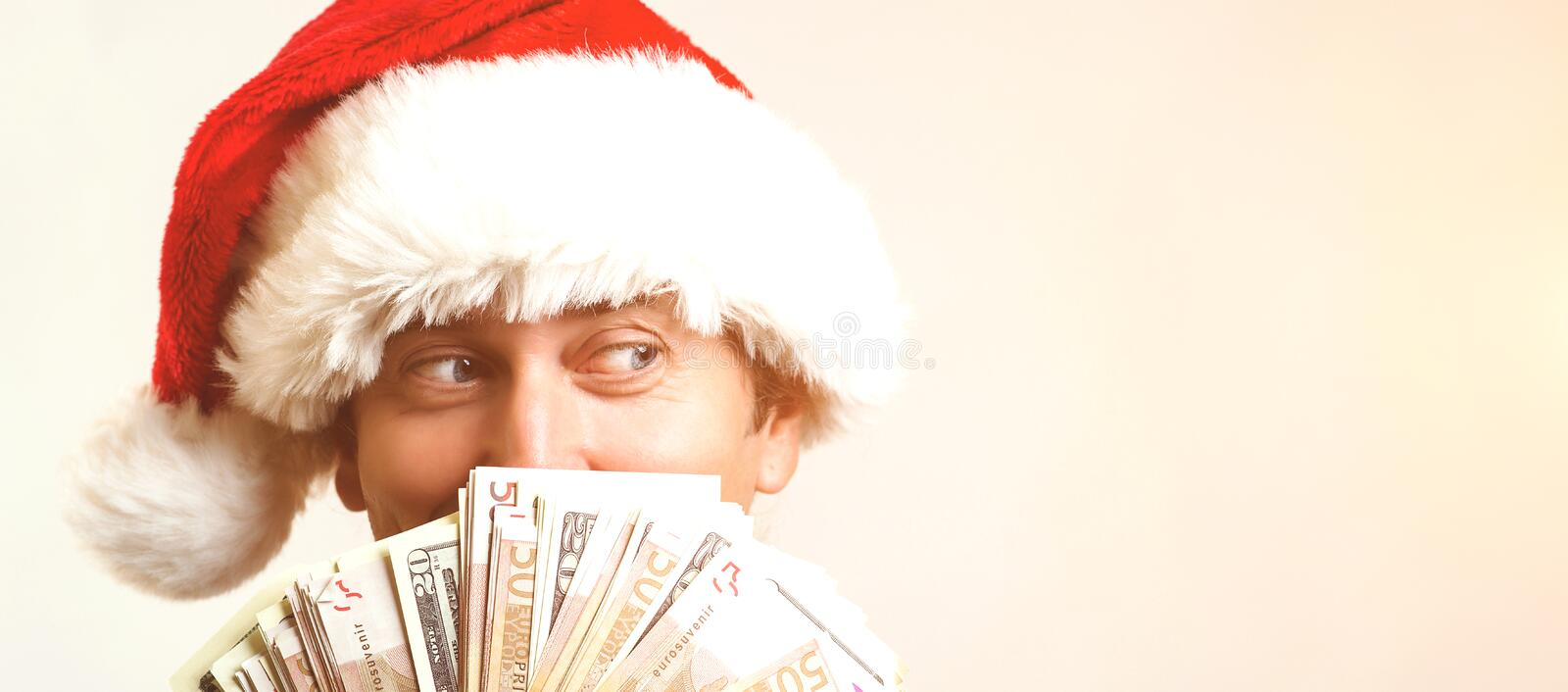 Young businessman in Christmas Hat covered his face with money over white background, copy space. Santa holding up fanned out hand stock photos