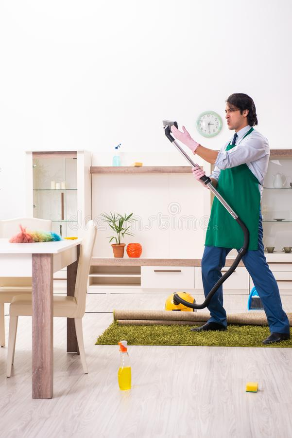 Young businessman cleaning the house. The young businessman cleaning the house stock photos