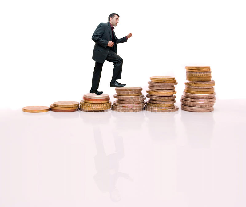 Young businessman climbing the steps made. A man, wearing a suit, climbing a steps made of coins stock photos