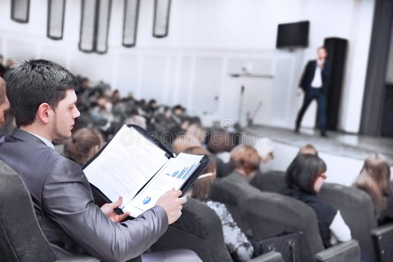 Young businessman with clipboard sitting at business presentation. stock photos
