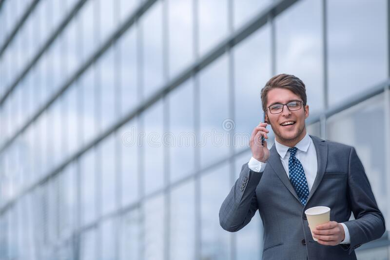 Young businessman with coffee talking on smartphone royalty free stock images