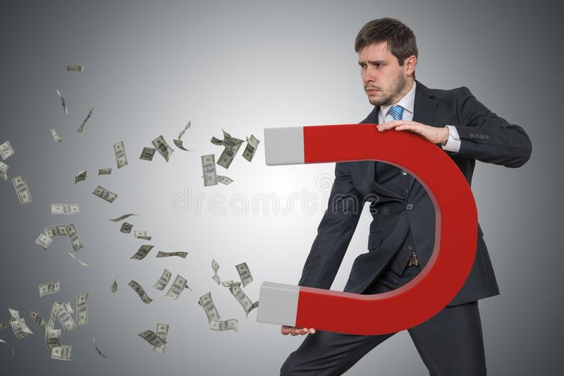 Young businessman is collecting money with big magnet stock photo