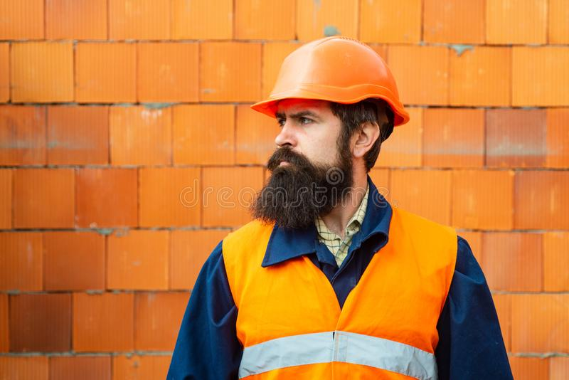 Young businessman construction site engineer, close up. Caucasian young builder standing. Worker portrait. Bearded royalty free stock images