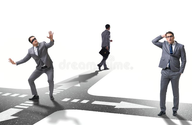 Young businessman at crossroads in uncertainty concept stock photos