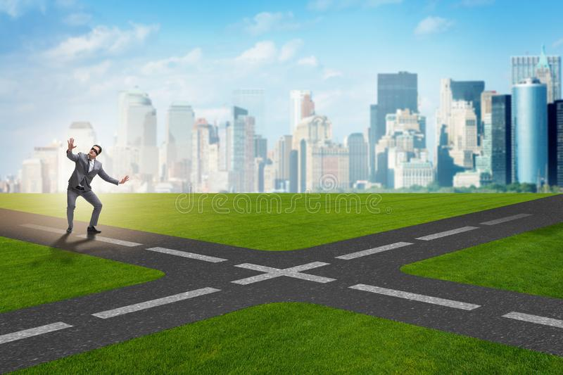 The young businessman at crossroads in uncertainty concept. Young businessman at crossroads in uncertainty concept stock photos
