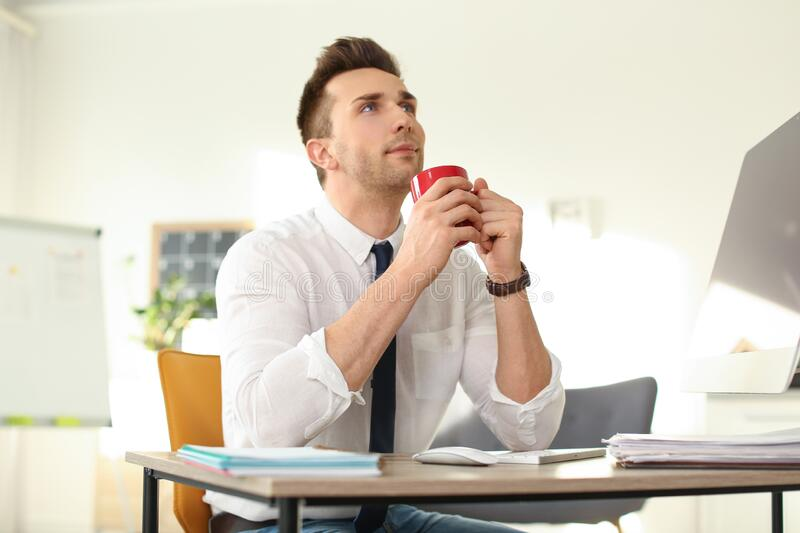 Young businessman with cup of drink relaxing at table during break stock photo