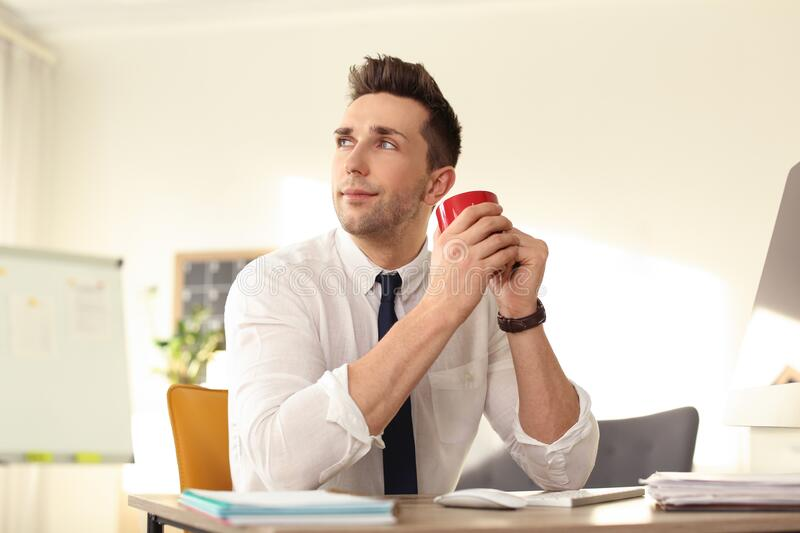 Young businessman with cup of drink relaxing at table during break stock image