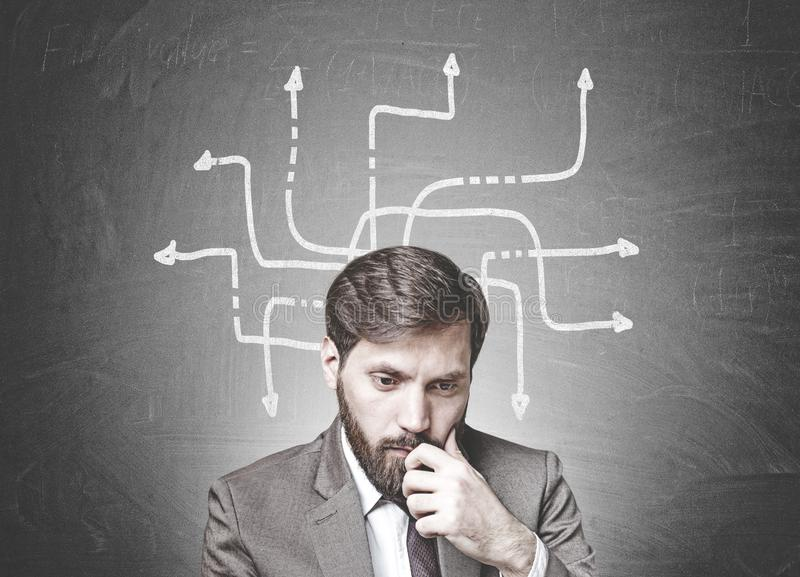 Bearded businessman in doubt, arrows, choice royalty free stock images