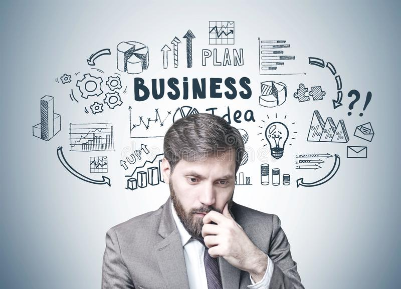 Bearded businessman in doubt, business idea. Young businessman with dark hair and a beard wearing a suit is thinking. A gray wall background with a business idea stock images