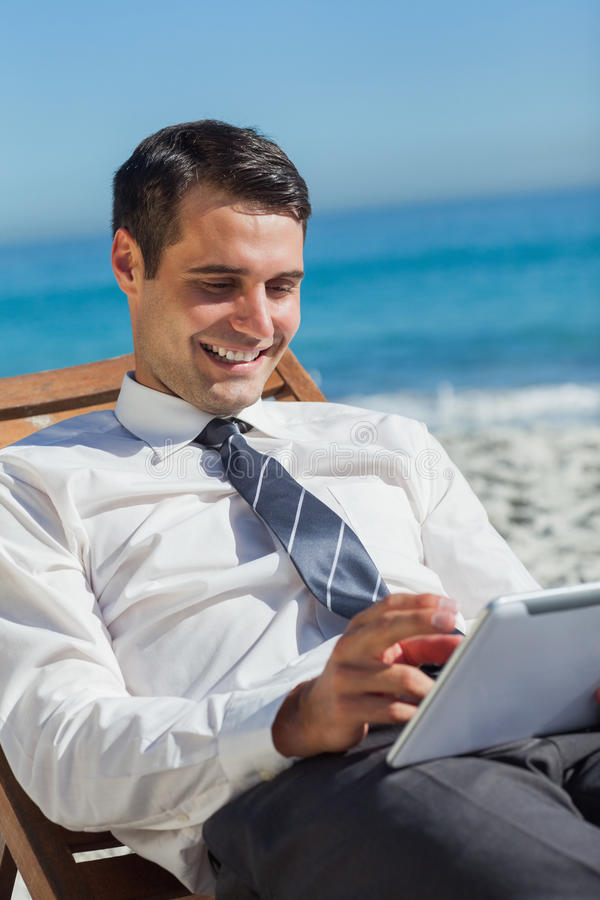 Young businessman on a deck chair using his tablet stock photography
