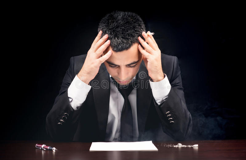 Young Businessman In Depression Smoking And Reading Contract Before Signing royalty free stock image