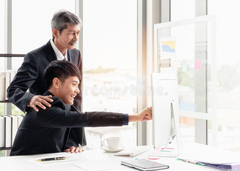 The young businessman discussing with his boss. The young businessman smiling and checking the point to the screen. He is discussing with his boss on the desk in royalty free stock photo