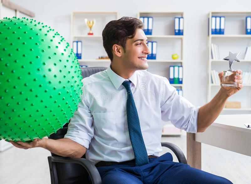 Young businessman doing sports stretching at workplace. The young businessman doing sports stretching at workplace stock photos